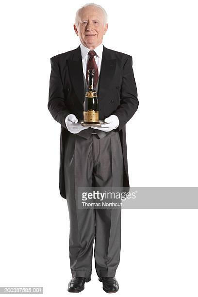 senior male butler carrying bottle of champagne, smiling, portrait - tail coat stock pictures, royalty-free photos & images