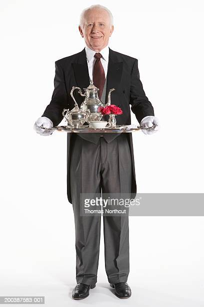 Senior male butler carrying teapot on serving tray, smiling, portrait