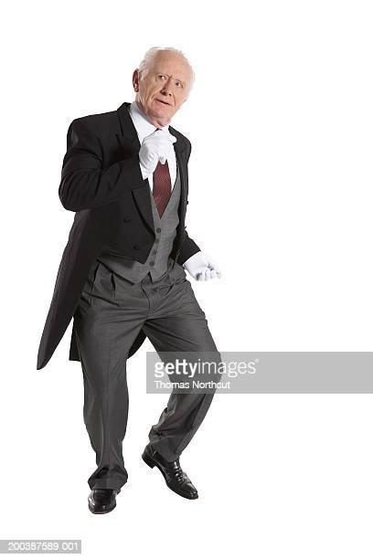 Senior male butler dancing, looking up