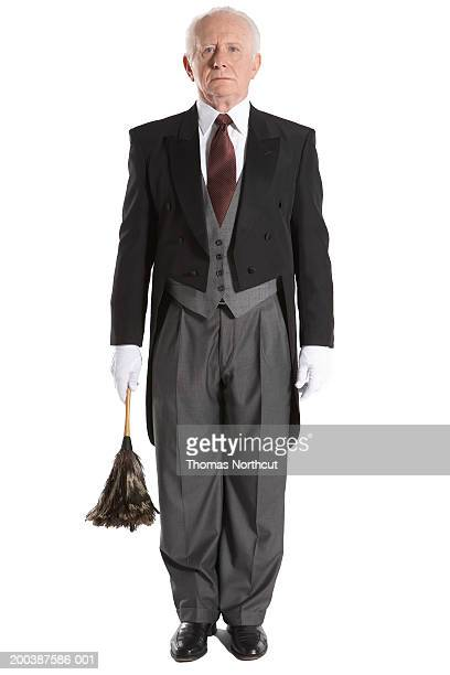 senior male butler holding feather duster, portrait - tail coat stock pictures, royalty-free photos & images