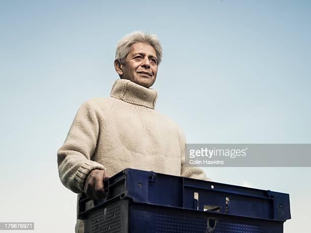 senior male carrying crate - sleeve stock pictures, royalty-free photos & images