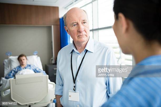 Senior male consultant listening to nurse in hospital