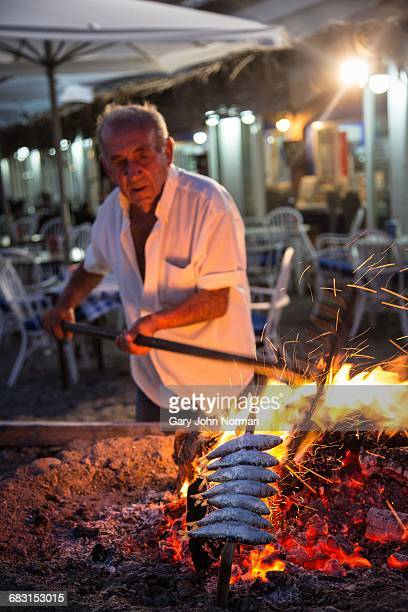 Senior male cooking sardines on wood fire