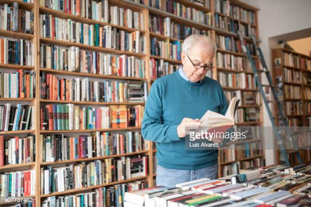 senior male customer reading book against bookshelf - reading glasses stock pictures, royalty-free photos & images