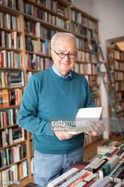 senior male customer reading book at bookstore