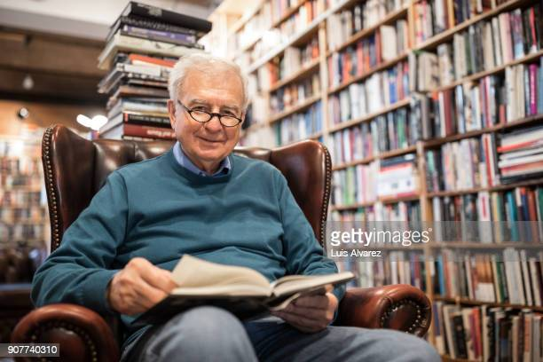 senior male customer reading book on armchair - einzelner senior stock-fotos und bilder