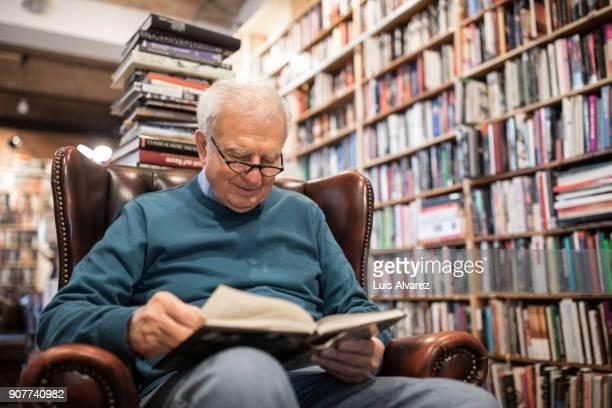 senior male customer sitting on armchair reading book - einzelner senior stock-fotos und bilder