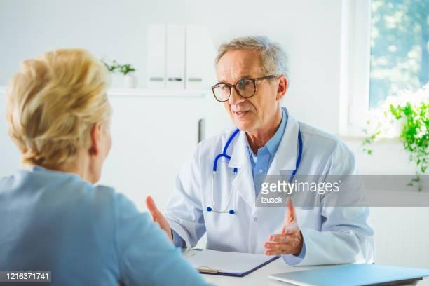 senior male doctor explaining health inssue - izusek stock pictures, royalty-free photos & images