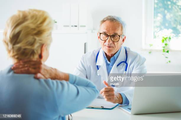 senior male doctor explaining health issue - izusek stock pictures, royalty-free photos & images