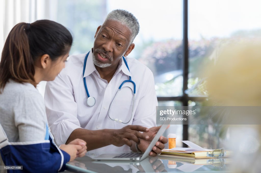Senior male doctor explains symptoms to patient using computer : Stock Photo