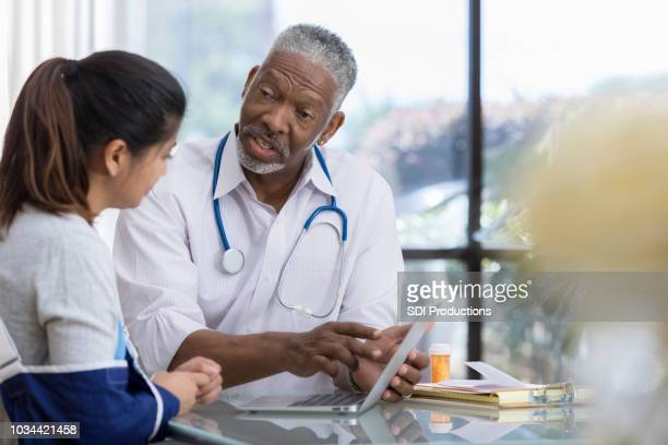 senior male doctor explains symptoms to patient using computer - arm sling stock pictures, royalty-free photos & images