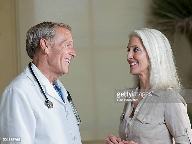 Senior male doctor reassuring mature woman patient