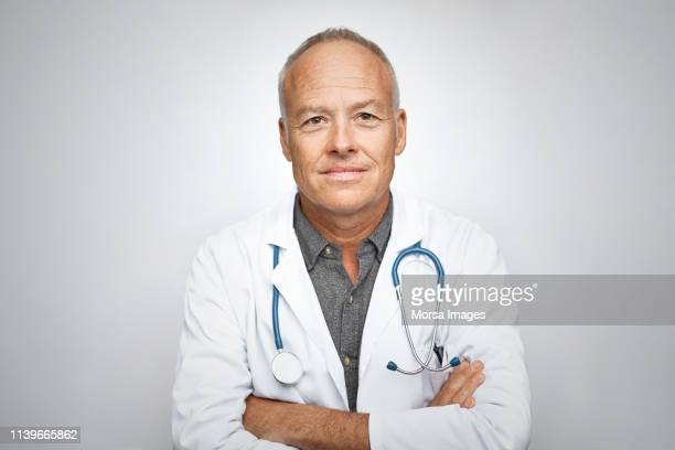 senior male doctor smiling on white background - dokter stockfoto's en -beelden