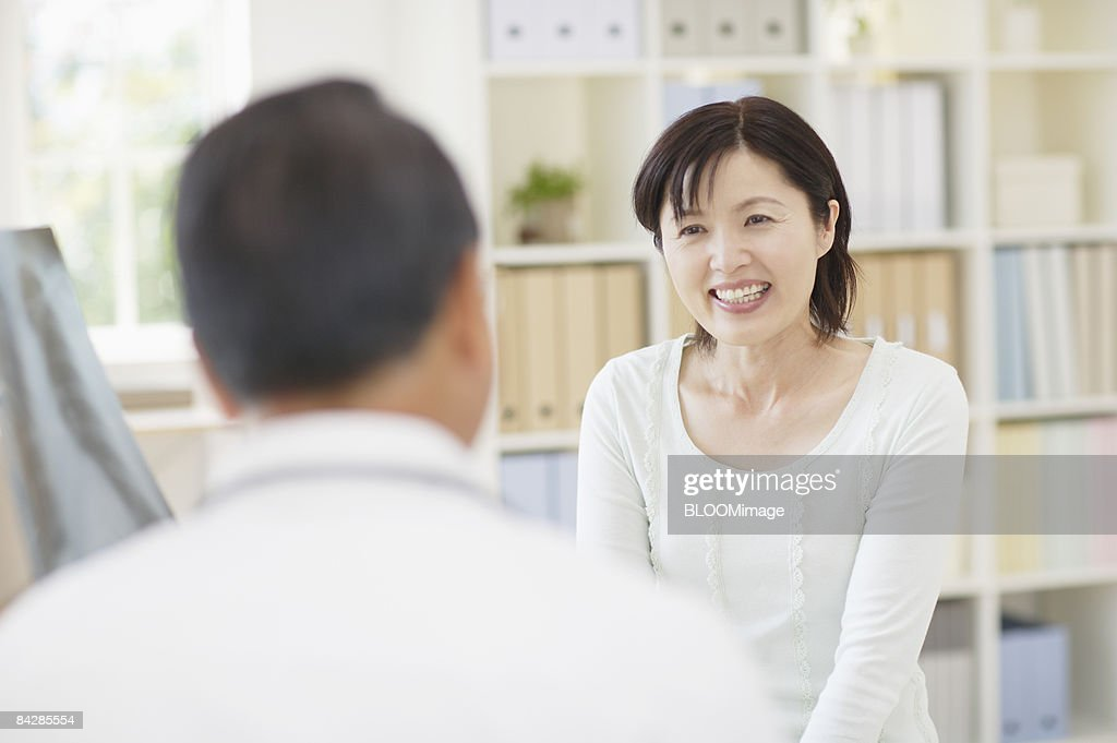 Senior male doctor talking to patient, focus on background : Stock-Foto