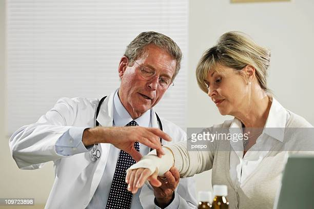 senior male doctor treating female patient