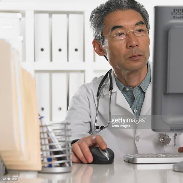 Senior male doctor using computer