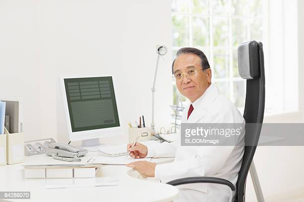 Senior male doctor working in office