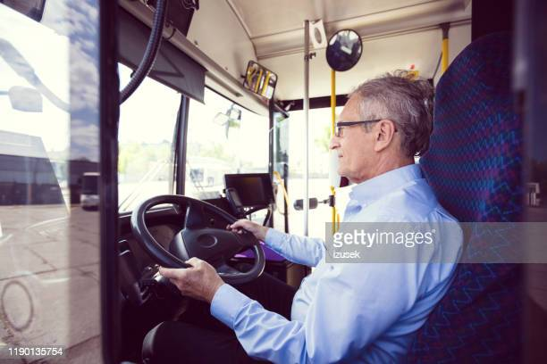 senior male driver driving bus - driving stock pictures, royalty-free photos & images