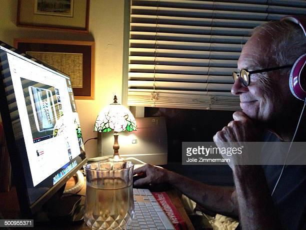 Senior male enjoying Internet music at night