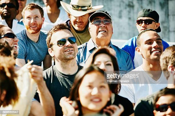 Senior male fan in crowd watching soccer match