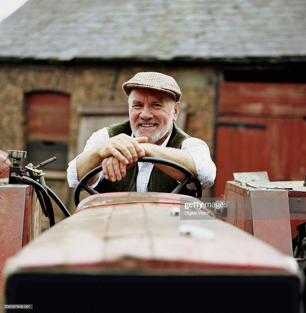 Senior male farmer sitting in tractor, smiling, portrait : Stock Photo