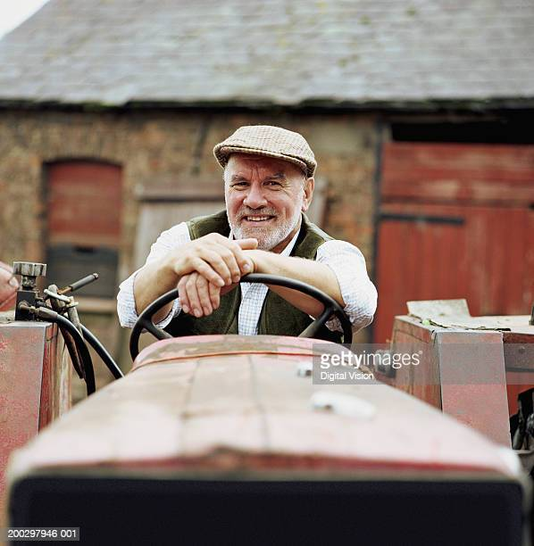 Senior male farmer sitting in tractor, smiling, portrait