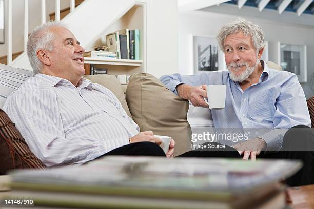 Senior male friends having coffee and chat