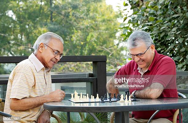 Senior male friends playing chess on patio