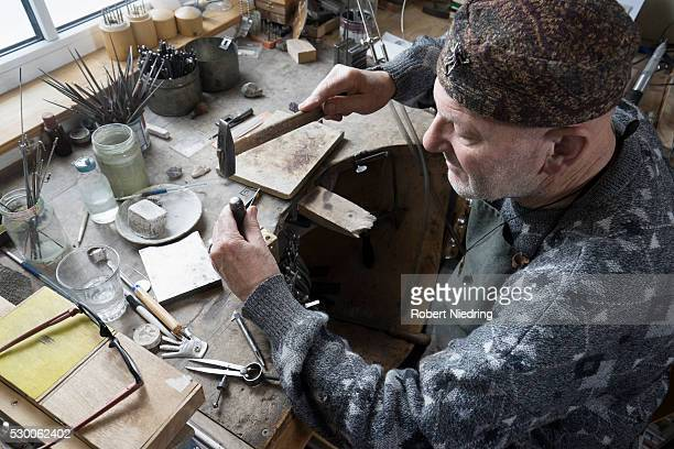 Senior male goldsmith hitting punches in workshop, Bavaria, Germany