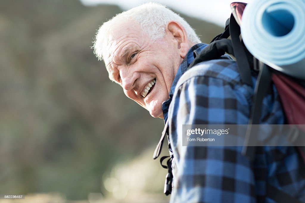 Senior male hiker climbing hill : Stock Photo