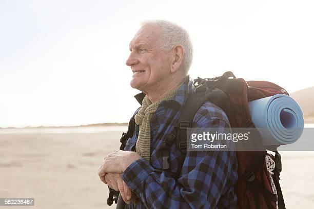 Senior male hiker resting on beach