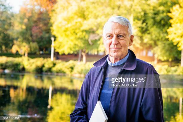Senior male holding book in park on Autumn day
