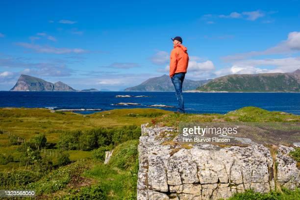 senior male in orange orange jacket standing on a top looking out over the ocean at sommarøy in northern norway - finn bjurvoll stock-fotos und bilder