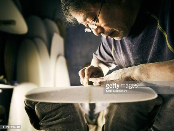 a senior male is shaping a surfboard - ポジティブなボディイメージ ストックフォトと画像