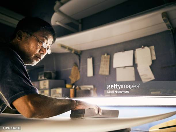 a senior male is shaping a surfboard - 美術工芸 ストックフォトと画像