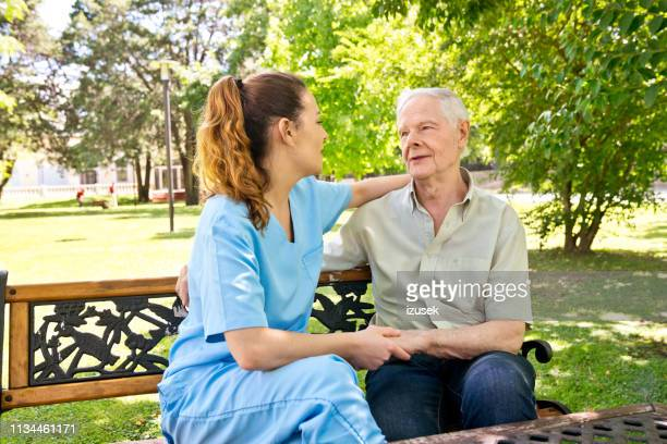 senior male looking at female nurse holding hands - izusek stock pictures, royalty-free photos & images