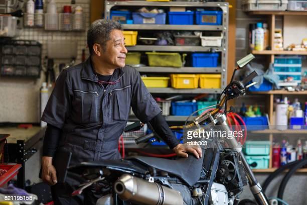 Senior male mechanic in his motorcycle repair shop