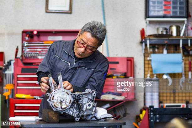 Senior male mechanic repairing a motorcycle engine in a small garage.