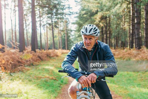 senior male on bike in forest - actieve ouderen stockfoto's en -beelden