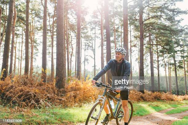 senior male on bike in forest - land stock pictures, royalty-free photos & images