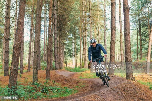 senior male on bike trail in forest - riding stock pictures, royalty-free photos & images