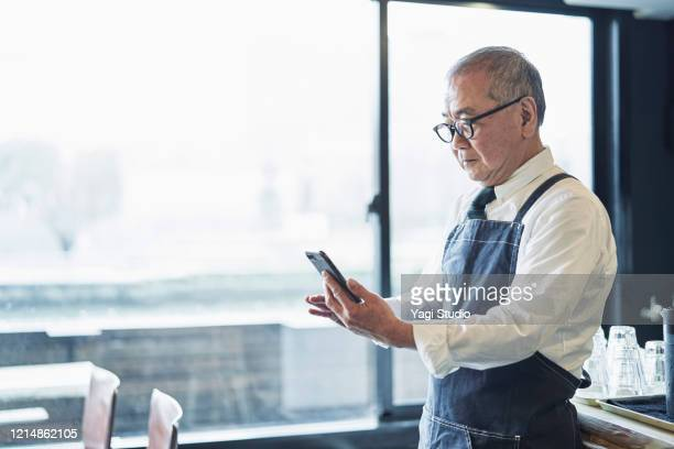 senior male owner working in cafe - disruptaging stock pictures, royalty-free photos & images