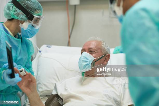 senior male patient enjoying video call from hospital bed - medical oxygen equipment stock pictures, royalty-free photos & images