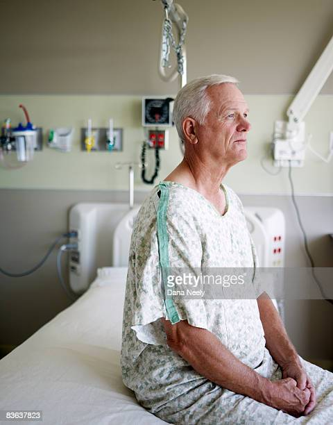 senior male patient sitting on bed in hospital - patience stock pictures, royalty-free photos & images