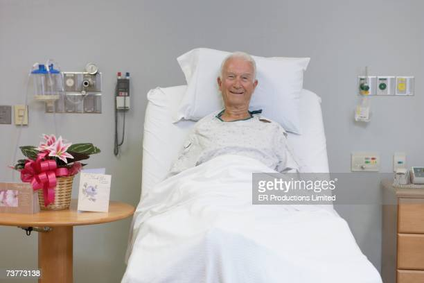 Senior male patient smiling in hospital bed