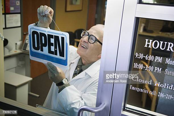 Senior male pharmacist hanging 'Open' sign in shop door, elevated view