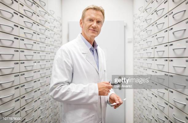 senior male pharmacist working at drug store - laborkittel stock-fotos und bilder