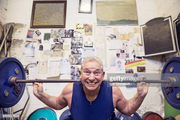 Senior male powerlifter lifting barbell on shoulders in gym