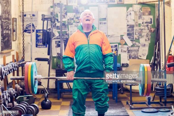 senior male powerlifter struggling to lift barbell in gym - trainingsanzug stock-fotos und bilder