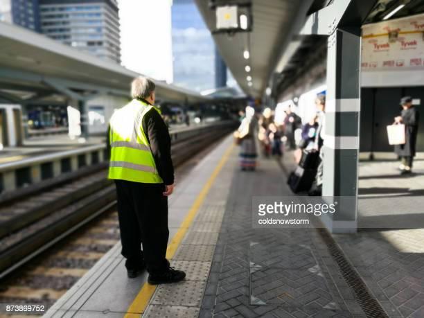 senior male railway employee wearing fluorescent vest on railroad platform at london bridge, london, uk - station stock photos and pictures